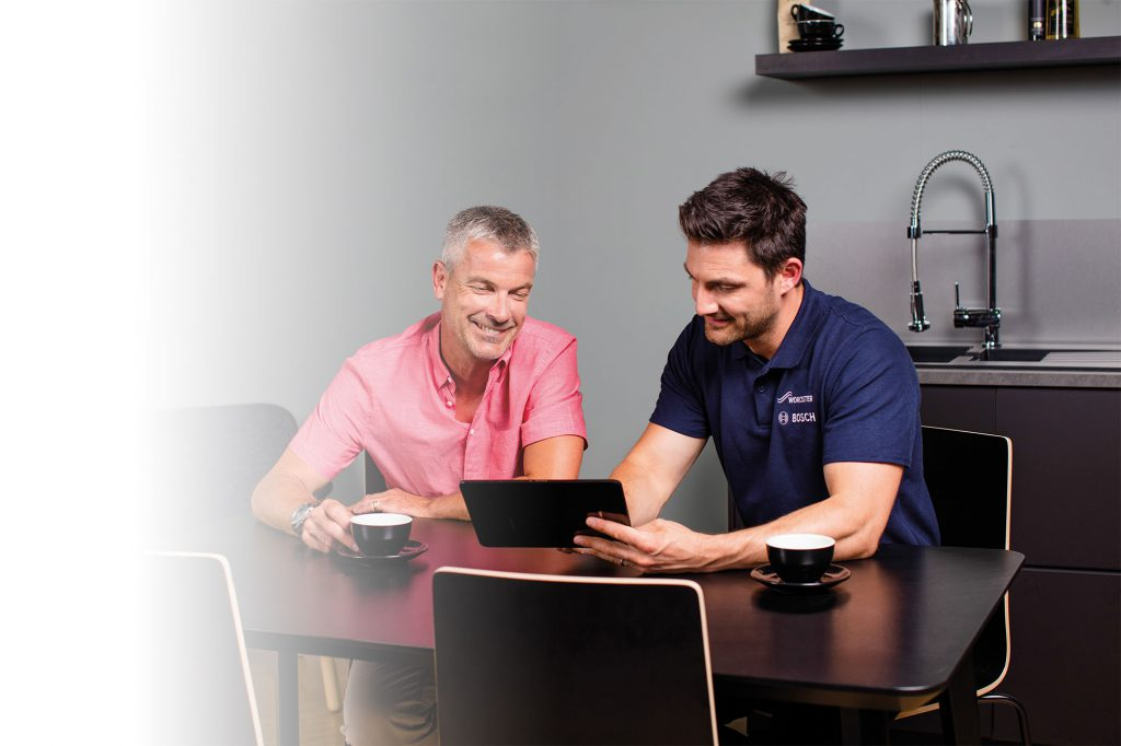Plumber and engineer discussing a boiler installation quote with a customer