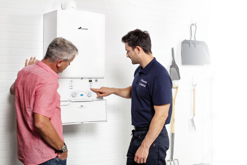 Plumber and engineer carrying out gas fire service and boiler service