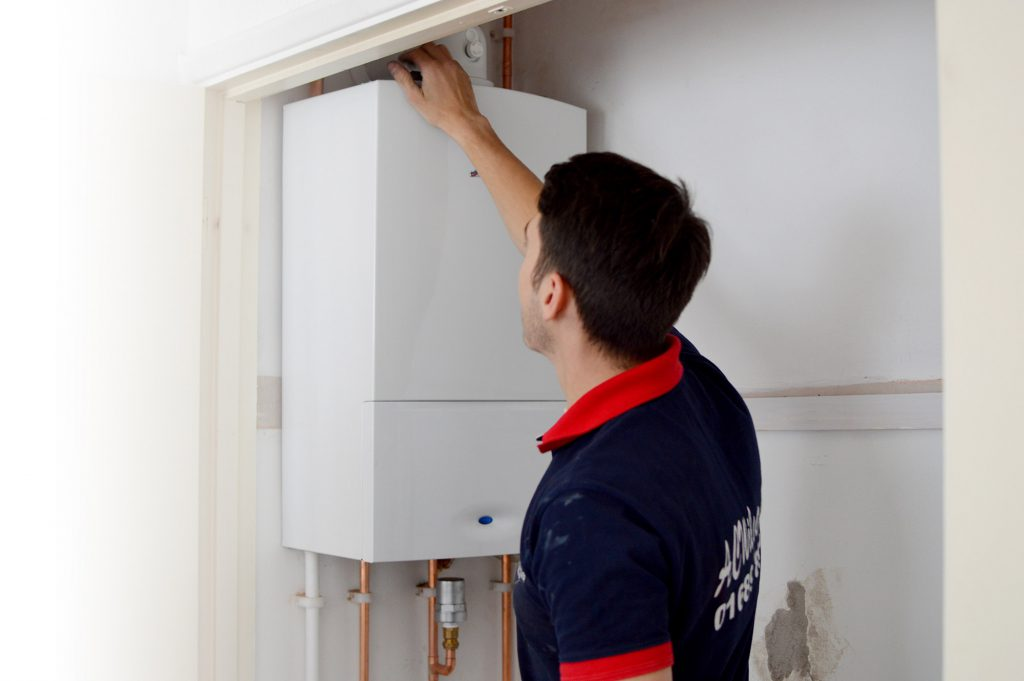A.C. Wilgar plumber and engineer inspecting the flue on a boiler