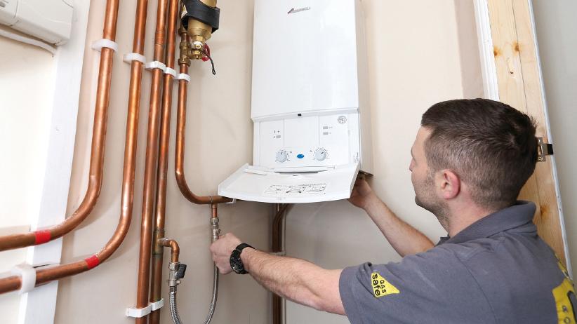 Engineer and plumber repressurising a boiler heating system