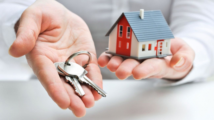 Landlord holding a small model house and a set of keys